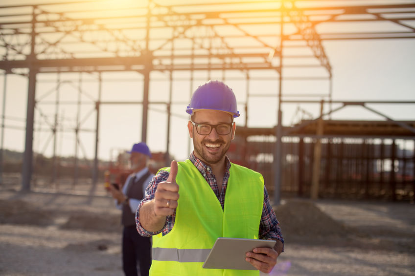 Engineer with thumb up on building site
